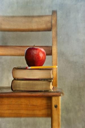 アップルとビンテージ学校椅子上の古い本を感じる