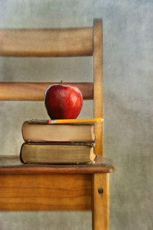 Apple and old books on school chair with vintage feel photo