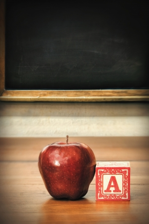 Delicious red apple on old school desk photo