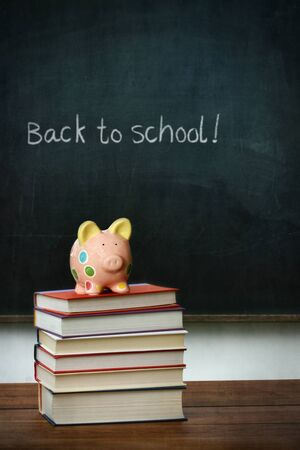 Piggy bank and books in front of chalkboard photo