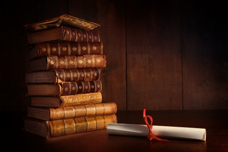 Pile of old books and diploma on desk Stock Photo