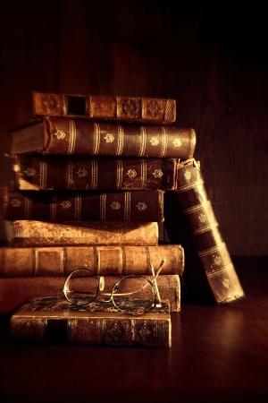 老眼鏡で机の上の本の古いスタックします。