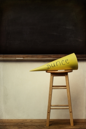 behave: Yellow dunce hat on stool with chalkboard in background