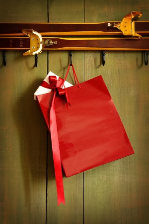 Red shopping bag hanging on hook on green wood background photo