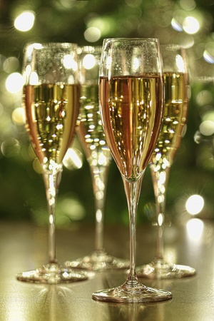 Glasses of champagne sparkle with festive background