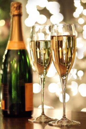 Copas de champán y la botella con el fondo festivo Foto de archivo