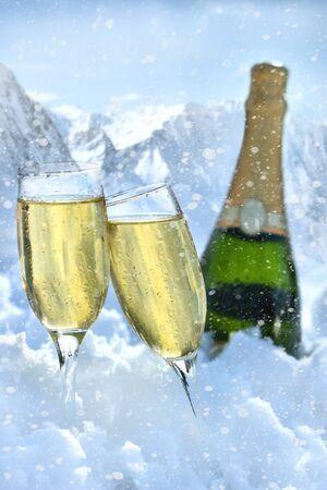 Twee glazen champagne in de sneeuw met berg op de achtergrond