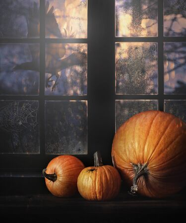 hollows: Different sized pumpkins in window for Halloween night