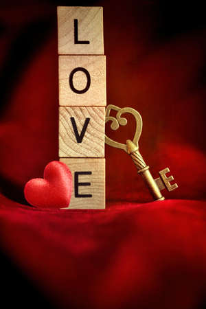 Gold key with wooden block letters that spell the word love photo