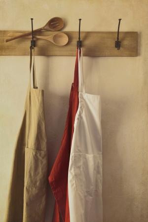 mandil: Delantales de cocina colgados en ganchos con aire vintage Foto de archivo