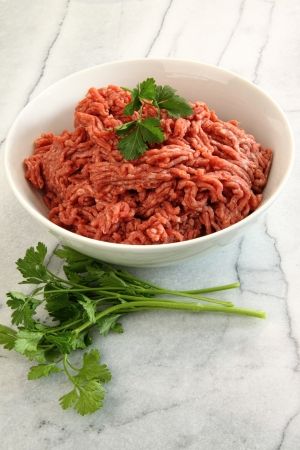 raw: Close up of raw ground beef on marble cutting board  Stock Photo