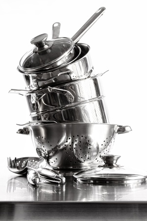Stack with stainless steel pots and pans on white background Stock Photo