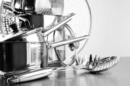 Edelstahl-Töpfe und Geschirr auf dem Tisch