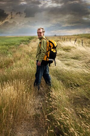 Man looking back and smiling on a prairie country road  photo