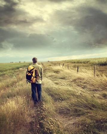 lejos: Hombre caminando por la carretera nacional en los praires