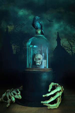 Creepy glass bell jar with crow and skeleton hands photo