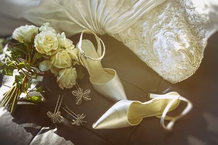 結婚式の靴の椅子の上の白いバラの花束を