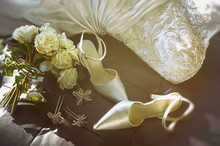 Wedding shoes with bouquet of white roses  on chair
