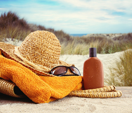 Straw hat with towel and lotion at the beach