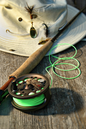 flyfishing: Close-up of fly-fishing reel and rod with canvas hat
