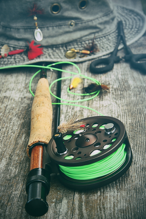 Fly fishing reel with old hat and equipment on bench  photo
