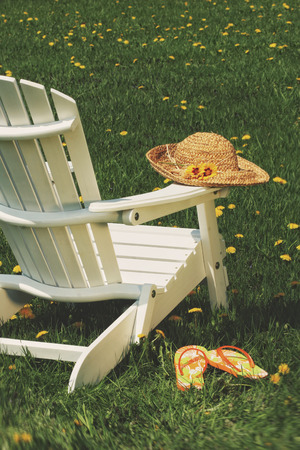 adirondack chair: Straw hat on adirondack chair in the grass Stock Photo