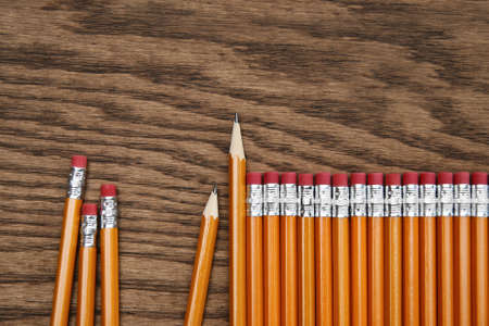 upright row: A row of red pencils on wooden surface