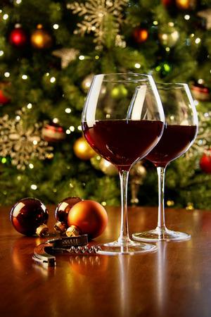 バック グラウンドでのクリスマス ツリーでテーブルの上の赤ワインのガラス 写真素材