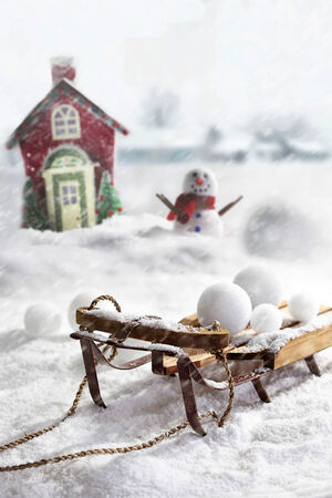 snowballs: Wooden sled and snowballs with snowman and wintery background