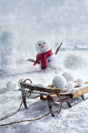 snowballs: Wooden sleigh and snowballs with snowman and wintery background Stock Photo