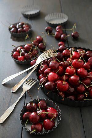 Fresh  cherries in aluminum plates on table