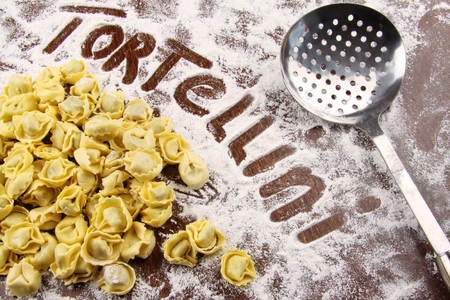stuffed tortellini: Fresh tortellini and utensil with flour on wooden table