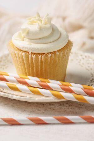vanilla cupcake: Closeup of vanilla cupcake with orange straws Stock Photo