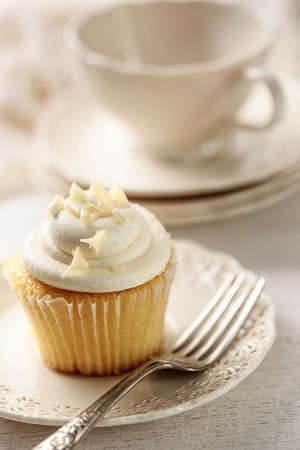vanilla cupcake: Closeup of vanilla cupcake with tea cup in background