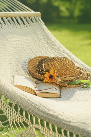 straw the hat: Straw hat and book on lace hammock