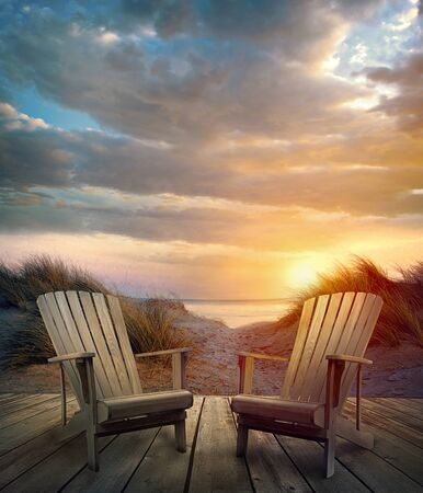 Wooden deck with chairs sand dunes and ocean at sunset
