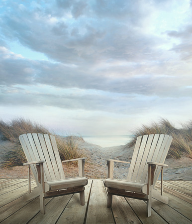 adirondack chair: Wooden deck with chairs sand dunes and ocean at sunset