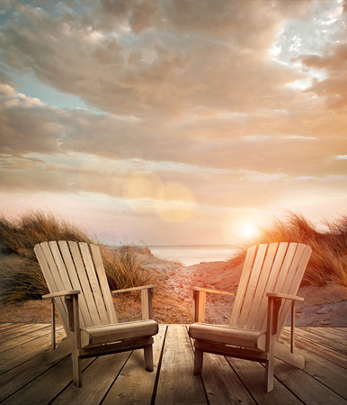 deck chairs: Wooden deck with chairs, sand dunes and ocean in background
