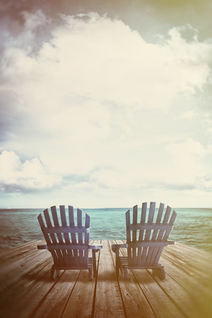 Blue adirondack chairs on dock with vintage textures and feel Stock Photo