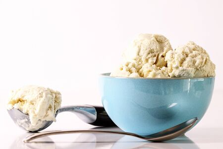 Vanilla ice cream in blue bowl with scooper and spoon