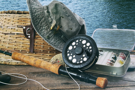 color image fish hook: Hat and fly fishing gear on table near the waters edge