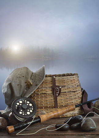 color image fish hook: Fly rod with creel and equipment on wood table