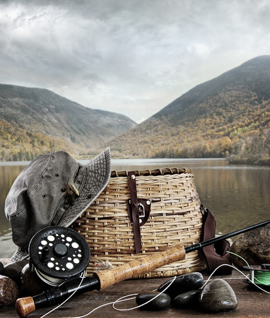 fly fishing: Fly rod with creel and equipment on wood table