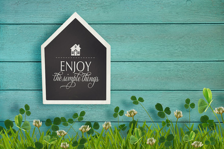 shaped: House shaped chalkboard and grass on wooden background Stock Photo