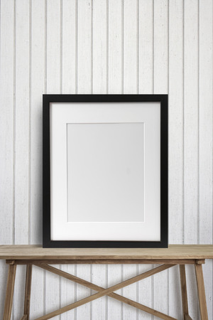 Black picture frame with on wooden table Standard-Bild