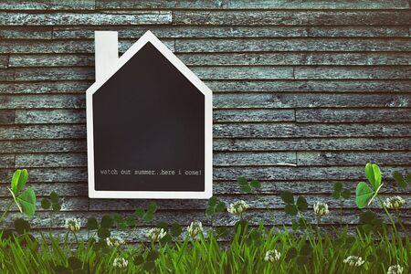 shaped: House shaped chalkboard on wooden plank background