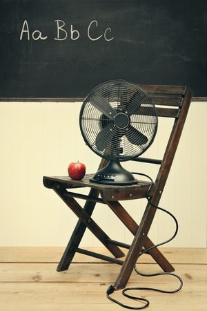 dirty room: Old fan with apple on chair in school room