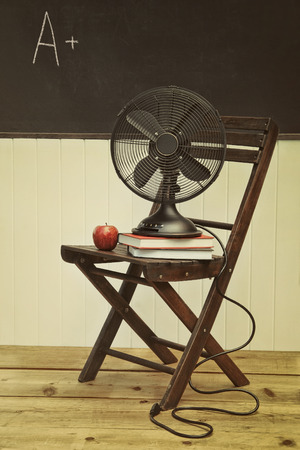 vintage objects: Old fan with apple and books on chair in school room