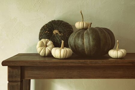 gourds: Green pumpkins and small gourds on wooden table Stock Photo