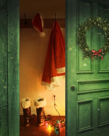 botas: Abrir puerta rústica con Santa sombrero y ropa colgando de ganchos